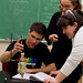 Professor Tara Kisbaugh, Ph.D., works with students during a chemistry lab.
