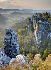 Sandstone Morning (HDR, Saxon Switzerland, Germany) (Xindaan) Tags: wood morning travel light sky sun mist mountain holiday mountains color tree green nature colors beautiful beauty fog clouds forest sunrise germany landscape geotagged outdoors deutschland dawn licht nationalpark spring nikon sandstone rocks europe day nebel tripod saxony natur himmel wolken berge sachsen dust nikkor landschaft sonne wald sonnenaufgang idyllic morgen sandstein 2009 baum brouillard tranquil hdr elbe bastei manfrotto frhling felsen eroded schsischeschweiz  rathen d300 elbsandsteingebirge saxonswitzerland photomatix 1685 1685mm 1685mmf3556gvr afs1685mm geo:lon=1407282338