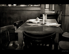 still from an unknown film (moggierocket) Tags: wood light bw stilllife berlin monochrome bar paper table newspaper still pub mood candle chairs empty atmosphere d200 cinematic cosy timeless cinemacafe noperson 2bdasest hourofthesoul fakefilmscene