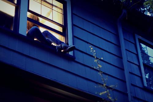Fotografía de una chica saliéndose por una ventana de su habitación en mitad de la noche