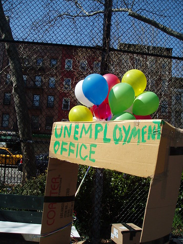 "A carboard box with a window cut in it that says ""unemployment office."""