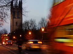 Magdalen Bridge, Oxford at dusk. Traffic includes a bus, cars and a bicycle.