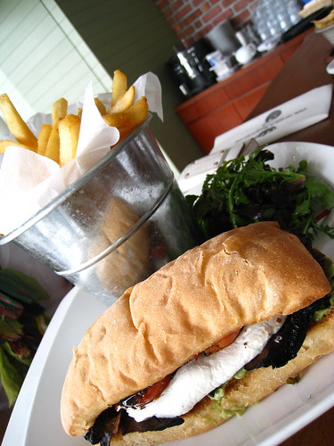 Sandwich of Grilled Brie Cheese, Avocado & Portobello Mushroom served with Chips