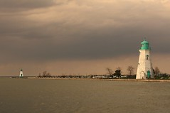 lighthouse (we own the sky) Tags: trees light sky lighthouse white house green cars water yellow coast horizon far