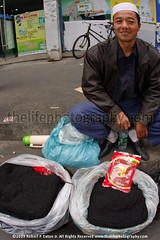 Muslim Chinese Street vendor selling his goods. (thelifephotography dot com) Tags: guangzhou china street smiling sittingdown guangdong vendor selling vendors middleaged chinesemuslim musilim traditionalhat whathat ethnicmonority openbags