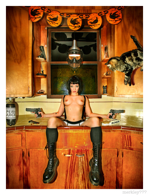 Violet Blue - Rude Girl in The Kitchen Sink Next to a Liter of Perv Juice Holding 2 Pistols Loaded w/ Boner Bullets Under Halloween Decor, Hanging Battle Mask Lamp, Throwing Stars, Taser, Knives & Diamond Brass Knuckles as The Alex The Cat Floats in