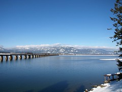 The Shores of Lake Pend Oreille (Designer Michael) Tags: bridge winter lake snow water noon lakependoreille meltingsnow mountainrange funinthesun sandpointidaho