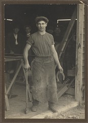 """Les Darcy at the blacksmith shop door"", East Maitland, ca. 1910 / Victor Studios (State Library of New South Wales collection) Tags: trestle apron cap workshop boxer horseshoe celtic mallet legend folkhero statelibraryofnewsouthwales xmlns:foaf=httpxmlnscomfoaf01 irishinaustralia foaf:depicts=httpnlagovaunlaparty1468813 lesdarcy"