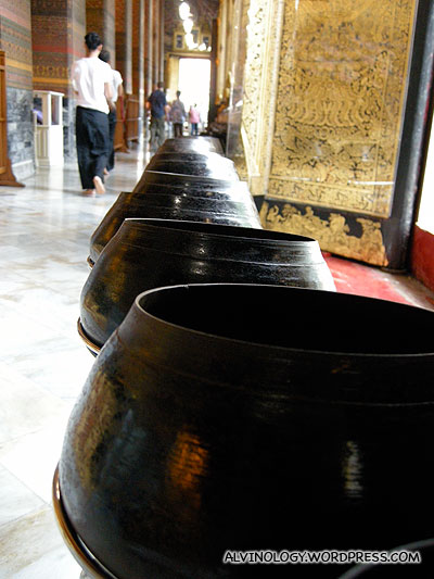 There are rows of alm bowls in front of the sleeping Buddha for making donations