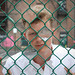 Tom almost behind a fence