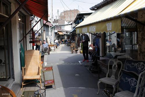 Bon nombre de vendeurs sont assis sur des chaises, dehors, surveillant plusieurs stands à la fois