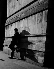Man - wall - shadow (Ian Brumpton) Tags: street leica uk shadow england blackandwhite bw london blancoynegro silhouette wall angel lumix blackwhite noir britain pavement candid streetshots streetphotography silhouettes streetportrait streetlife sidewalk londres shadowplay angelwings longshadows streetphotographer panasoniclumix infinestyle dmclx3 scattidistrada