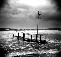 Banzai beach (massi_pugliese) Tags: sea blackandwhite bw mer white black 120 6x6 film beach clouds square holga lomo lomography surf mare waves kodak surfer flag grain surfing 66 bn squareformat bianco 2009 nero spiaggia bianconero quadrato onde 400iso pontile bandiera grana realidad palabra pellicola kodaktrix400 analogico nuovole medioformato bwart autaut ficticia banzaibeach aplusphoto ilfordwarmtone jpeggy cartabaritata massimilianopugliese massipugliese