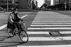 Rush (Go-tea 郭天) Tags: qingdao huangdao pedestrian crossing bicycle bike man basket old cold coat hat winter sun sunny ride riding lines shadow alone lonely cars taxi traffic light signal empty street urban city outside outdoor people bw bnw black white blackwhite blackandwhite monochrome asia asian china chinese shandong canon eos 100d 24mm prime movement rush
