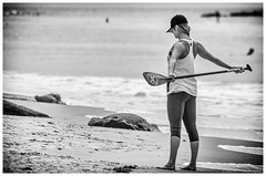 Stretching Routine, Laguna Beach California (Cozy61) Tags: stretching routine laguna beach california fitness woman sportswear pacific ocean monochrome nikon d2x d5100 werner paddle baseball cap hair braid barefoot sand rocks water female bottom posterior buttocks glutes taut biceps triceps rotation keep fit exercise