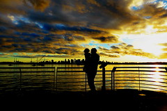 Unconditional love at sunset (peggyhr) Tags: ocean blue boy sunset sky white canada man black skyline vancouver clouds gold bc silhouettes cranes railing crèmedelacrème thegalaxy 50faves peggyhr flickrawardgroup peaceawards 100commentgroup super~six☆stage1☆bronze redlevelno1 frameit~level01~ niceasitgets~lev1 blinkagainp1 p1070515a thebestshotpost1award5
