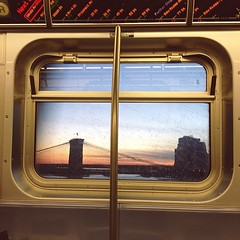 Brooklyn Bridge with Sunset from Subway (nycbone) Tags: nyc bridge sunset urban window brooklyn train river subway square americanflag squareformat commute brooklynbridge eastriver mta iphoneography instagramapp uploaded:by=instagram foursquare:venue=4de23e57e4cd056f743ea6f3