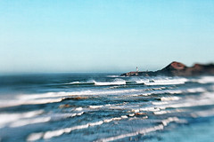 by that long scan of the waves (1crzqbn **away**) Tags: blue sunlight lighthouse seascape blur color nature lensbaby rocks waves shadows textures 7d composer hss 1crzqbn sliderssunday vision:beach=0815 vision:outdoor=099 vision:clouds=0821 vision:ocean=0806 vision:sky=083 bythatlongscanofthewaves yakinaheadlight