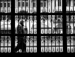 behind bars (Magdalena Roeseler) Tags: world street camera city portrait bw white black eye square lens photography prime schweiz flickr moments fotografie faces candid creative zug commons going olympus scene snap best crop squareformat vivian eyed 12mm moment 18 unposed left 45mm omd tog decisive tstreet maier explorescout strassenfotografie flickriver iphoneography streetog