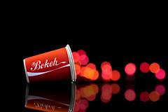 spill happines (brescia, italy) (bloodybee) Tags: 365project paper cup bokeh cocacola coke logo brand reflection mirror stilllife red black drink soda