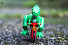 Dino Rider (jezbags) Tags: lego legos dinosaur trex toystory toy story bike bikeride cycle bicycle canon60d canon 60d 100mm closeup upclose minifigure minifigures macro macrophotography macrodreams macrolego floor ground outside green red wheel