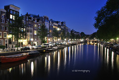 Singel (JdJ Photography (www.jdj-photography.nl)) Tags: auto city bridge trees wet water netherlands car amsterdam speed evening living canal bomen europa europe driving apartments traffic streetlights country nederland nat bicycles land bluehour innercity brug avond singel mokum continent province fietsen stad noordholland gracht benelux wonen verkeer rijden snelheid canalhouses grachtengordel binnenstad grachtenpanden provincie northholland appartementen amsterdamcentrum straatverlichting grootamsterdam blauweuur agglomeratie