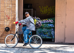 Santa Ana - A Bicyclist Passes Graffiti Covered Dumpster (www.karltonhuberphotography.com) Tags: 2017 action backpack bicycle bicyclist brickwall citystreets downtown dumpster graffiti karltonhuber lookingatme male man movingleft outdoors peoplewatching riding sidewalk southerncalifornia stopaction streetphotography streetscene theoc urban