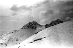 04a3371 35 (ndpa / s. lundeen, archivist) Tags: nick dewolf nickdewolf bw blackwhite photographbynickdewolf film monochrome blackandwhite april 1971 1970s 35mm europe centraleurope switzerland swiss alpine alps graubünden grisons stmoritz easternswitzerland suisse schweitz mountains peaks snow snowy snowcovered skiresort skiarea skislopes skiing landscape sky clouds slopes swissalps