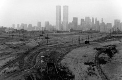 Empty railroads, tumbleweeds, shacks and telephone poles to the horizon like crosses in Jerusalem. Lower Manhattan and the World Trade Center hover in the background over this scene of utter abandonment. Jersey City. March 1975 (wavz13) Tags: oldphotographs 1970sphotographs 1970sphotos oldphotography 1970sphotography vintagephotographs vintagephotos vintagephotography filmphotos filmphotography newyorkphotographs newyorkphotos oldnewyorkphotography oldnewyorkphotos vintagenewyork vintagemanhattan vintagenewyorkphotography vintagenewyorkphotographs vintagenewyorkphotos oldworldtradecenter vintageworldtradecenter twintowers originalworldtradecenter industrial industrialphotos industrialphotography oldfactories vintagefactories railroadphotos railroadphotography railroads vintagerailroads vintagerailroadphotography oldrailroads oldrailroadphotography oldbuildings vintagebuildings depressing bleak noir noire dark abandonedbuildings oldtrainstations vintagetrainstations antiquetrainstations abandonedtrainstations oldtrainterminals vintagetrainterminals antiquetrainterminals abandonedtrainterminals jerseycityphotographs jerseycityphotos oldjerseycityphotography oldjerseycityphotos oldjerseycity vintagejerseycity vintagejerseycityphotography urbanphotography urbanphotos urbanscenes cityphotography newjerseyphotographs newjerseyphotos oldnewjersey vintagenewjersey newjerseyhistory urbanwasteland abandonedrails abandonedrailroads abandonedtracks hiroshima nagasaki