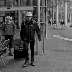 Hiking Boots (Akbar Simonse) Tags: people bw woman man holland blancoynegro netherlands monochrome hat station square couple zwartwit candid nederland streetphotography bn luggage amersfoort koffer trunck hoed hikingboots straatfotografie rolkoffer akbarsimonse