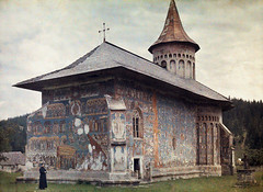 1934 - A priest stands beside a painted church built by Stephen the Great (narcis_gabriel) Tags: people male men history church architecture standing vintage painting outdoors one worship europe cross adult architecturaldetail military faith religion visualarts landmark romania tradition easterneurope oneperson backview closeupview balkanstates worshiping autochrome oneobject unrecognizableperson