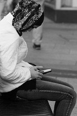 (Corah Louise Photography) Tags: street portrait blackandwhite bw woman white black girl photography alone sitting technology phone religion streetphotography jeans fancy sat