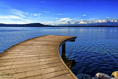 a curve in the blue (Tiziano Photography) Tags: blue sky panorama lake snow mountains reflections landscape lago pier nikon nuvole blu cielo neve curve riflessi montagna molo onde wawes d610 viverone cluouds lagodiviverone photographyforrecreationeliteclub nikond610 vision:sunset=0531 vision:beach=0606 vision:outdoor=099 vision:sky=0766 vision:ocean=0693