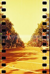 Sprockets & Skyscrapers Pt.III - The Mall (Cris Ward) Tags: road park street city uk red summer orange building london tower tlr film westminster yellow architecture analog 35mm point gold golden town lomo lomography warm britain flag perspective sunny landmark panoramic flags holes buckinghampalace lubitel stjamespark medium format analogue manual 60mm distance vanishing height xr lubitel166b themall sprocket filmstrip twinlensreflex sprockets sprocketholes redscale lomolab filmmarkings lomographyuk lomographyredscalexr50200
