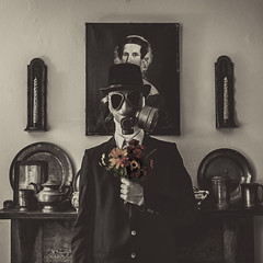 Messiahbolical (Mike Shaheen) Tags: flowers portrait blackandwhite white selfportrait black color me monochrome hat self square nikon fireplace mask antique top fake eerie gas suit tuxedo adobe tophat saturation gasmask concept 1855mm messiah conceptual tux pewter lightroom diabolical idk d90 conceptphotos vision:people=099 vision:face=099 vision:text=0652