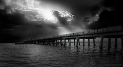 The Light in the Storm (JDS Fine Art Photography) Tags: bw blackwhite monochrome ocean sea water waterscape oceanscape seascape landscape bridge dramaticsky sky dramatic light illumination inspirational storm stormy moody atmosphere sunset clouds rays raysoflight lightrays
