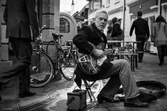 Is anybody listening? (Silver Machine) Tags: winchester hampshire streetphotography street busker busking guitar guitarist epiphone bigsby roland sitting outdoor people marvinbnaylor acoustic folk rock blackwhite bw mono monochrome fujifilm fujifilmxt10 fujinonxf35mmf2rwr