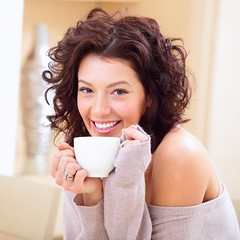 Young woman at home sipping tea from a cup (hyleysteaonline) Tags: beautiful beauty beverage caucasian coffee comfort comfortable cosy cup curly domestic dreaming drink female girl happiness happy healthy home house indoors knitted lady leisure looking morning one person portrait pretty recreation redhaired relaxation relaxing rest sip sitting smiling sweater tea warm wellbeing white woman