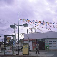 Uniondale (Luis_maldonado) Tags: street light summer sky newyork color 120 6x6 tlr film monochrome clouds analog corner mediumformat square purple cloudy pedestrian oldman monochromatic longisland gasstation pole 120film pump medium gasoline nassau yashica 120mm velvia50 uniondale colorfilm twinslensreflex