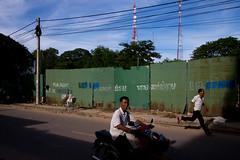 (kravse) Tags: street travel summer two people green fence cambodia southeastasia candid streetphotography run motorcycle moped siemreap whiteshirt olympusomdem5