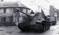Two Jagdpanther Ausf.G1, with Zimmerit coat and camouflage, belonging to 2.Kompanie/schwere Heeres-Panzerjäger-Abteilung 654 rolling at high speed through the streets of Bourgtheroulde-Infreville, Haute-Normandie, France. July 1944.