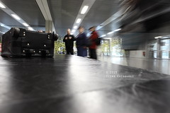 Lost (Elios.k) Tags: light people motion black france color reflection travelling horizontal standing canon hall airport movement waiting dof many room luggage depthoffield passengers indoors slowshutter wait getty toulouse baggage blagnac conveyorbelt claim lowangle 5dmkii