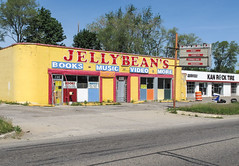 Used books and tapes, not anymore. (Tim Kiser) Tags: 2013 20130526 dorthighway flint flintmichigan geneseecounty geneseecountymichigan highway54 highwaym54 img0506 jellybeans jellybeansbookstore jellybeansusedbooks jellybeansusedbookstore kanrocktire m54 may may2013 michigan michiganhighway54 michiganroute54 midmichigan route54 routem54 statehighway54 stateroute54 bookstore booksmusicvideomore booksmusicvideoandmore businessname businesssign centralmichigan colorinarchitecture colorfulbuilding colorfulstorefront downtownflint driveway eastcentralmichigan formerbusiness paved pavement sign storefront street sunny usedcdstore usedcds usedbookstore usedcassettestore usedcassettetapes usedtapes usedvideostore usedvideocassettes usedvideos usedvideotapes vacantbuilding vacantbusiness weeds yellowandred yellowandredbuilding yellowredandblue