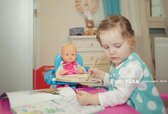 blonde toddler girl pretending to draw with her doll in her bedroom (Fon-tina) Ta
