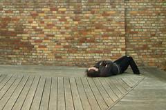 Sleeping Man (sterreich_ungern) Tags: sleeping red man brick guy wall grey wooden nap stage plate holz mauer backstein bhne