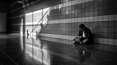 Lost in the Music (Anne Worner) Tags: anneworner blackandwhite ricohgr silverefex architecture bw candid concentrated crosslegged floor hallway indoors leadinglines man mp3player music reflection shadows sitting streetstreetphotography tiles wall wideangle airport chicago ohare traveller killingtime