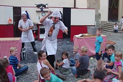 Don't piss off the cook! (Jumpin'Jack) Tags: angry mad half crazy bugeyed black eye pissedoff cook chef poisedto kill throw dough ata haples spectator murder intent funny tie paper cap kitchen table covered witha chequered checkerboard cloth big cookbook steps stairs openair street cooking show performance lacuisine kids children spectators watching