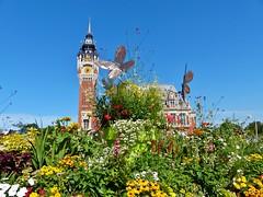 Belfort en stadhuis met bloemenpracht en kunst versierde perken