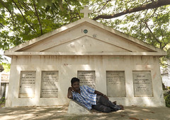 Young Man Lying In Front Of A French Grave In A Cemetery, Pondicherry, India (Eric Lafforgue Photography) Tags: trees people india color colour cemetery horizontal outside outdoors graffiti necklace memorial day branch quiet cross watch deadleaves christian number barefoot garve lying hindu takingabreak oneperson pondicherry driedleaves colorimage pondichry lookingatcamera indianpeople onemanonly frenchcolony oneyoungman puducherry frenchwriting shadeoftrees oneadult unionterritoryofpondicherry