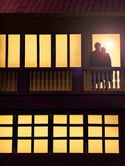 Enjoying the Sunset (Steve Taylor (Photography)) Tags: art digital window brown contrast roof yellow man lady woman singapore asia silhouette airport changi terminal sunst sun lensflare couple lovers